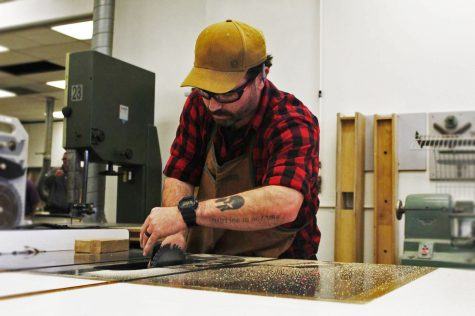 Travis Smith, a woodworking major at Cerritos College, cuts planks for a dresser.