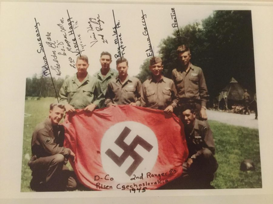 Members+of+Dog+Company%2C+including+Vince+Hagg+and+Roy+Miles+from+Tyrone%2C+pose+for+a+photo+holding+a+captured+Nazi+battle+flag+in+Czechoslovakia+in+1945.+