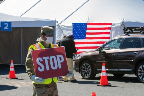 Private First Class Jose Rivera assists with traffic control at the University at Albany COVID-19 Drive-thru Test Site in support of the New York National Guard's domestic operation in response to the coronavirus outbreak.