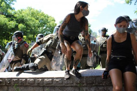 A woman is forced over a wall as state troopers force protesters off of the Capitol grounds during Saturday