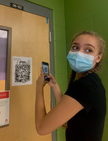 Sophomore Leylani Neris scans back into her classroom so administration can track where she has been and what she has touched.