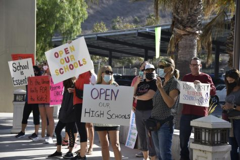 Parents opposed to an extension of online learning for high school students gathered outside the district office on Tuesday.