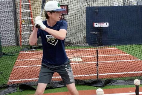 At the Indiana Baseball Academy in Westfield, junior Will Mayer prepares to hit off a tee. The Hit Trax machine in the background, similar to a golf simulator, will record and break down every element of his swing, helping him to improve his game.