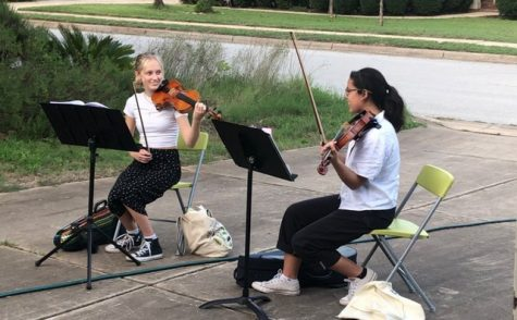 """Lucy Hamre (left) and Ileana Nicholson (right) share a knowing look as they preform their violin arrangements for a socially-distanced audience. The profits from the performances went entirely to charities and organizations.  """"It just felt really fitting that we do something that has monetary value to help organizations,"""" Nicholson said."""