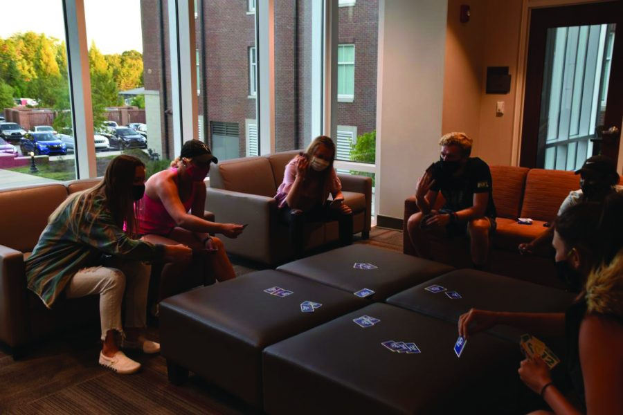 Friends play a card game in the freshman dorm Legacy Hall.