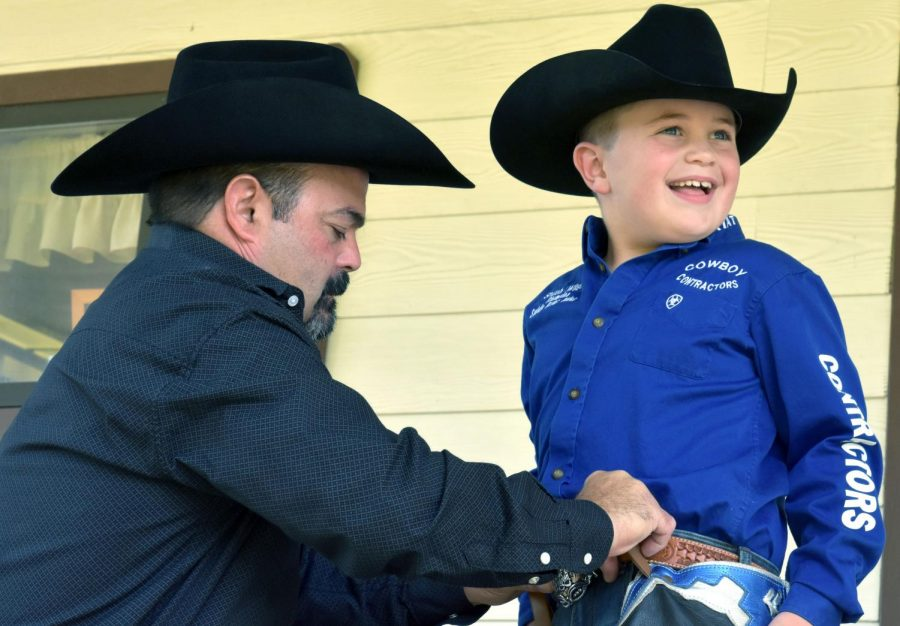 Jeff+Wilson+adjusts+the+gear+his+son+Shiloh%2C+7%2C+wears+each+time+he+competes+in+saddle+bronc+riding+at+rodeos.+His+father%2C+who+teaches+collision+and+refinishing%2C+retired+from+rodeo+in+2004.+He+was+a+saddle+bronc+champion+in+2002.+