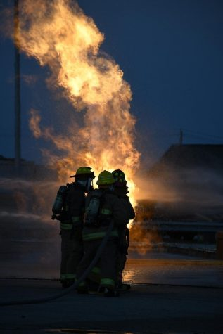 "Students from the LBJ Fire Academy work their way towards a propane fire, using fire hoses to control the blaze. The purpose of the drill wasn't to put out the fire, but to use the spray to get close enough to the propane tank to turn off its fuel source.  Five McCallum seniors, John Hughes, Thomas Lucy, Tex Mitchell, Molly Odland and Will Russo, participated in the live fire skill day, where they put into practice what they've learned during the two year student-sharing program at LBJ High School.  ""Being in the live fire gave me really intense adrenaline,"" senior Molly Odland said. ""I was the head of my group, meaning I was in charge of directing the hose line at the fire while my group supported me from behind.""  Senior Will Russo, who also had the chance to lead the group, said that the drill felt like being in a hot car.  ""It wasn't all that scary since you were with a bunch of people, but it was kind of intimidating because there was nothing in between you and the fire but water,"" Russo said."