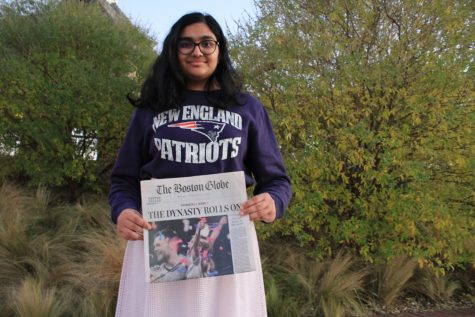 The Sidekick junior staff writer Anjali Vishwanath shows her team loyalties with a sweatshirt and newspaper article describing the New England Patriots' 2019 Super Bowl win at Andy Brown East. Vishwanath moved from Massachusetts to Texas in 2018, but finds that her loyalty remains with New England sports teams.