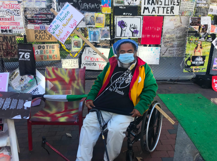 Philipos Melaku-Bello sits in his wheelchair in front of the poster-covered fences. Melaku-Bello has spent years protesting for various causes outside of the White House, particularly those pertaining to racial and immigration injustices.