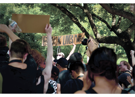 PROTESTS IN AUSTIN: Protesters hold up Black Live Matter signs at a march against police brutality. The pro- tests began after the death of George Floyd and continued throughout the summer.