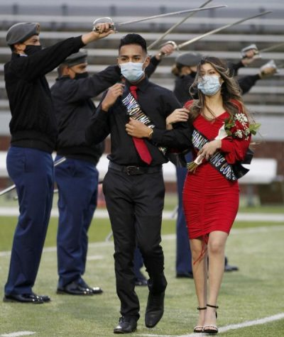 Alexandra Saenz, 12, and Daniel Orona, 12, walk down the field during the  homecoming coronation ceremony on Oct. 23.