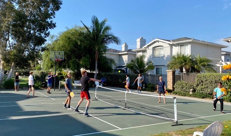 Wyatt+and+his+friends+are+playing+pickleball+at+a+local+court.+He+likes+playing+pickleball+because+everyone+is+pleasant+to+play+with%2C+and+he+often+makes+new+friends.+