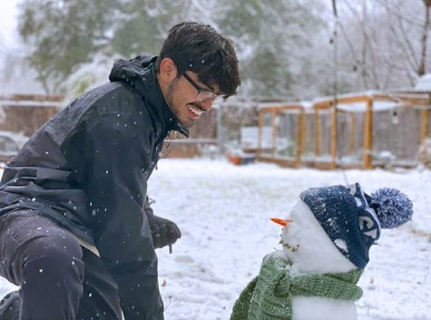 SUNFLOWER SEEDS AND TAMALES: Senior Daniel Dueñas-Lujan inspects his handiwork building a snowman with all the finishing touches. Dueñas said that Sunday