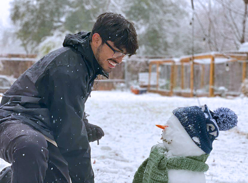 SUNFLOWER SEEDS AND TAMALES: Senior Daniel Dueñas-Lujan inspects his handiwork building a snowman with all the finishing touches. Dueñas said that Sunday's snow caught him off guard and that after realizing it was showing he decided to build a snowman, which we have to say looks pretty darn lifelike almost as if Dueñas was meeting Olaf on the set of Frozen. What's the secret to Dueñas' snowman success?