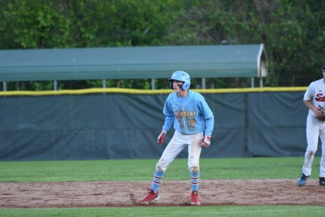 "Preparing to run to the next base, senior Elliot Krewson watches the next pitch to the batter. Krewson has been playing baseball since he was 3 years old. ""Winning a game, especially when your team is struggling, is a great feeling. However, winning isn"