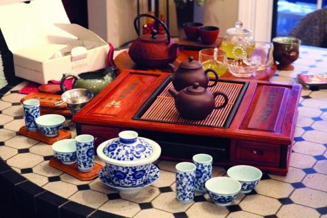 Ikue Shirayanagi shows the different types of teapots and teacups that are used for different types of tea. These are authentic Chinese teapots and teacups. The brown teapots are used for oolong tea, and the white and blue ceramic cups are used for jasmine tea.