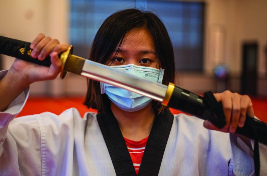 Sophomore+Avery+Guo+poses+with+a+sword+in+her+dojang.+Guo+said+the+instructors+at+her+dojang+have+taught+her+how+to+properly+defend+herself+both+with+and+without+weaponry.