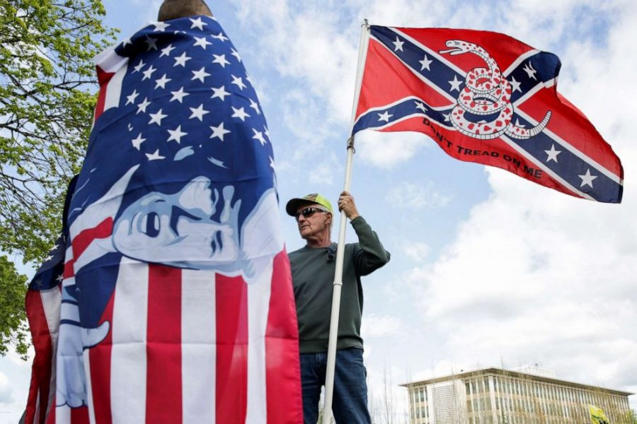 A+right-wing+protestor+holds+a+flag+that+combines+a+Gadsden+flag+from+the+American+Revolution+with+a+Confederate+flag+from+the+Civil+War.+Though+the+two+symbols%2C+historically%2C+contradict+each+other%2C+they+are+now+frequently+seen+together.+He+talks+to+another+man+holding+an+American+Flag+with+President+Trump%E2%80%99s+face+plastered+over+it.