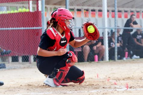 Carey Koenig '21 kneeling on the ground after catching the softball with her left hand.