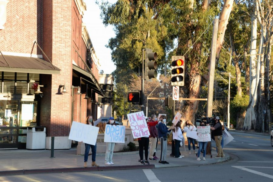 Parents+stand+on+the+corner+of+El+Camino+Real+and+Burlingame+Avenue%2C+holding+signs+to+advocate+for+the+reopening+of+high+schools.