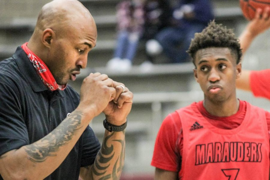 Assistant Basketball Coach James Singleton instructs junior Christian Weddington during the game on Feb. 2.