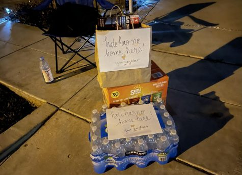 "The Si family is the latest victim in Ladera Ranch to severe anti-Asian harassment. Neighbors are uniting together to prevent these attacks by waiting in shifts outside of the targeted house. Members of the community often bring food for the volunteers. Pictured is a brown bag of food and case of bottled water with a label in front saying ""Hate has no home here!"" In the background, chains are pictured in the driveway, one of the many security measurements the Si family implemented as a deterrent to attacks."