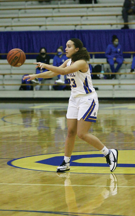 Riley Pennington, member of the women's basketball team and senior, passes a basketball to a teammate during a game. She said she thinks the demographics of Carmel explain why there may be underrepresentation of blacks in some sports at CHS.
