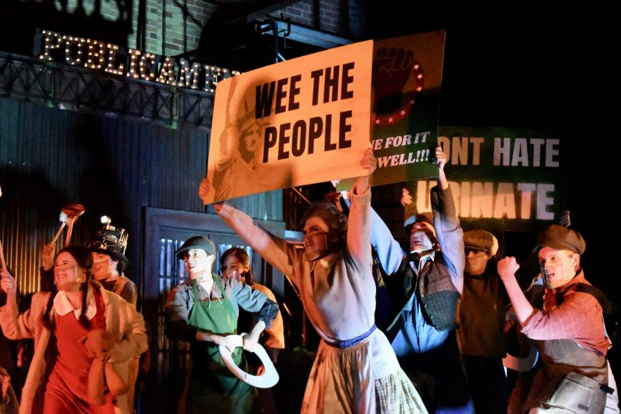 """WEE THE PEOPLE: Junior Amethyst Mellberg-Smith holds up a sign during a Urinetown scene involving a protest for the right to """"pee for free."""" Mellberg-Smith thinks that the show is a commentary on the current political climate. """"It's totally political satire,"""" Mellberg-Smith said. """"It's making fun of serious situations that are somewhat similar to things happening now, but in such a comedic and absurd way it really shows how messy politics and fighting for what's right can be."""" Mellberg-Smith said that while being on stage for the first time in a year was a rewarding experience, her favorite part of the production was spending time with her friends. """"Finally seeing people every day made all of the hard work feel effortless,"""" Mellberg-Smith said, """"and I can't wait to do it again!"""" Reporting by Samantha Powers."""
