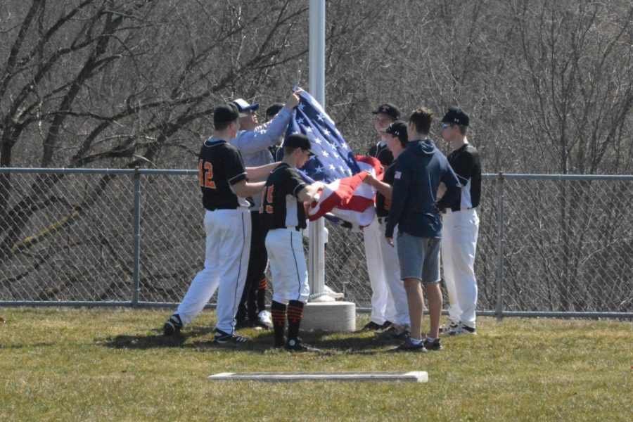TAHS+senior+baseball+players+raise+the+flag+at+the+flagpole+honoring+their+friend+and+teammate+Adam+Fink.