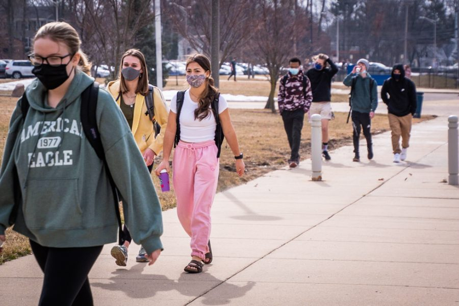 Ella Finger (9), Anna Phillips (9), Imran Kareem (10) and others walk toward the main entrance along with other in-person students. Masks are mandatory to reduce the risk of spreading COVID-19. Students and staff can temporarily put their mask off in an open area where they are alone to drink, switch masks or take a breather.