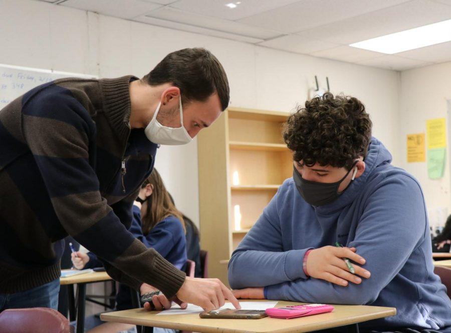 Easton+Gorman+helping+sophomore+Ethan+Malave+work+through+a+problem+during+class.