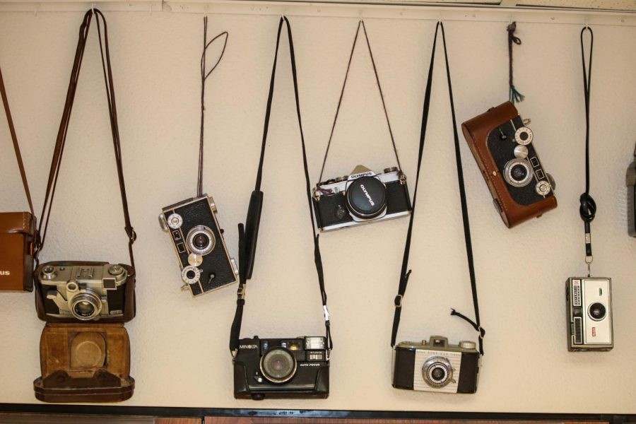 Photography teacher Kathy Toews keeps cameras on a wall in her classroom. They are all different ages and models.