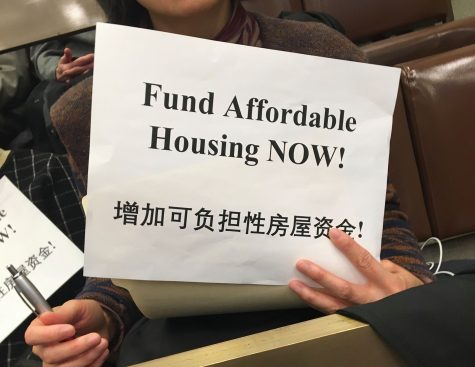 "Silent protestors in the crowd held signs that said ""Fund Affordable Housing NOW!"""