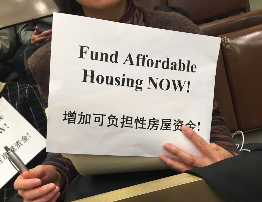Silent+protestors+in+the+crowd+held+signs+that+said+%22Fund+Affordable+Housing+NOW%21%22+