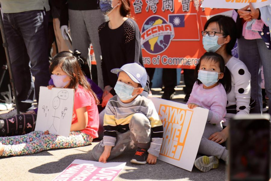 While listening to speakers, toddlers sitting on the ground hold signs to support Stop AAPI Hate efforts.