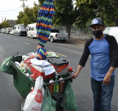 A seller stands with his cart on Crisanto street.  He has lived on the street for 25 years.