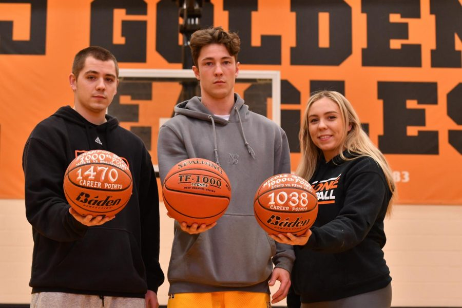 The Gripps: Brandon (2014), Damon (2021) and Nicole (2013) pose in the Tyrone Middle School gym with their 1,000 point basketballs.