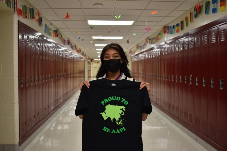 PROUD TO BE AAPI: Megan Wikowsky (12) is a part of the planning committee for Asian American Pacific Islander month in May and made t-shirts for students and staff to wear to support. She stands behind origami made by Audrey Lee (10)  hung in the ceiling tiles.