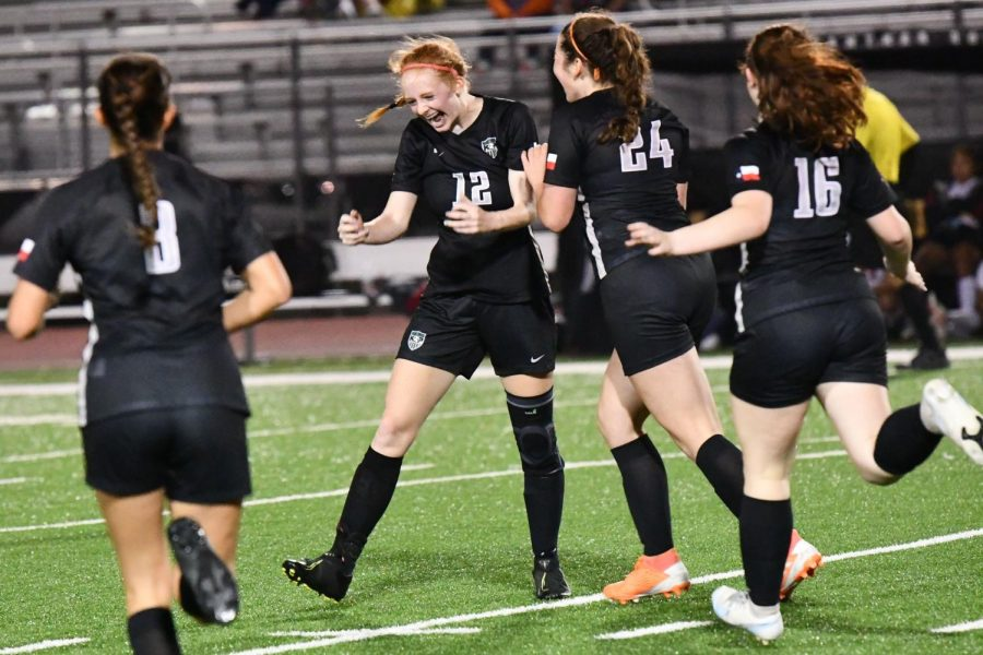 Emma Yeager pumps her first as her teammates rush to congratulate her after scoring her third goal against Porter on March 12. Her final goal of the game was her 41st of the year and put her atop the record books for goals in a season at Kingwood Park.