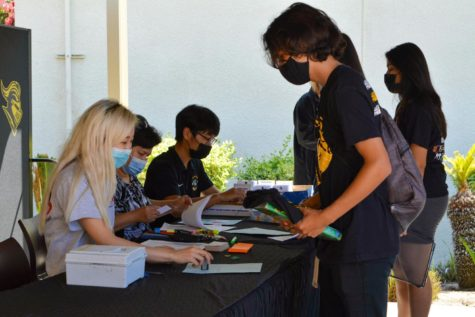 Senior Dominic Siañez (right) checks in with a South Coast Photography staff member at Lancer Day, Tuesday, Aug. 10, to take his ID picture. Despite the continuing spread of COVID-19's Delta variant, Siañez will be among the nearly 2,500 students who have enrolled at Sunny Hills for live classroom instruction.