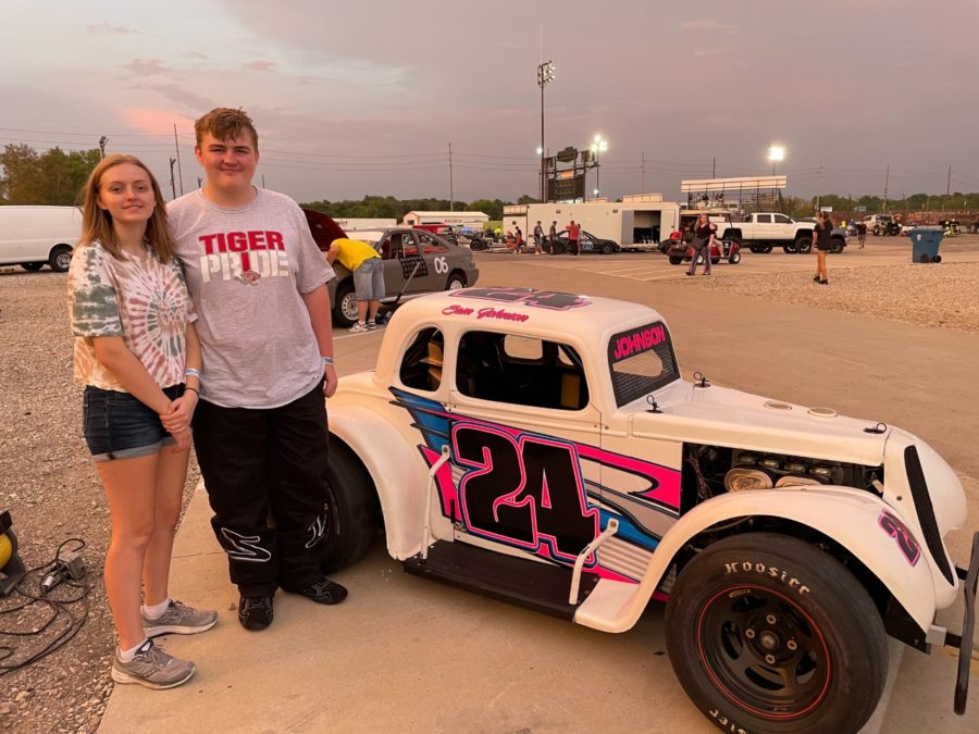 Sophomore Sam Johnson and his sister, senior Natalie Johnson, stand in front of Sam's Legend race car. Sam Johnson is the second youngest driver in his age group (ages 14 to 50.)