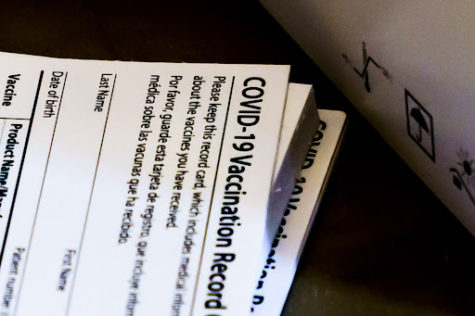 A stack of vaccination cards waits to be filled for the recipient