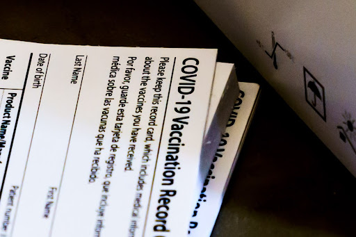 A stack of vaccination cards waits to be filled for the recipients records.