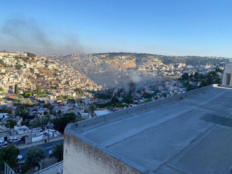 OVERLOOK: From the balcony of his dorm overlooking the Kotel, David Edwards 20 photographs smoke rising where fireworks had ignited grass fields after being launched from Silwan in East Jerusulam before Shabbat on May 14.