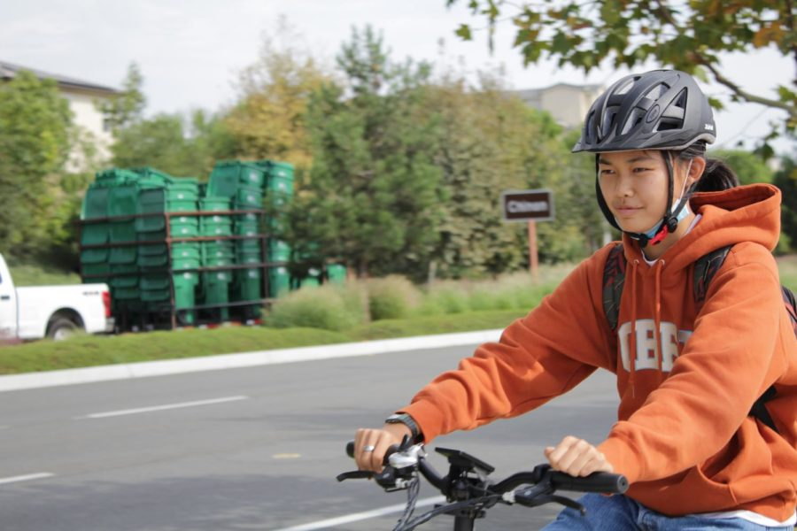 Sophomore Kaylin Wong rides her electric bike home from school along Irvine Blvd. on Oct. 6. The roadway abuts the Eastern Transportation Corridor Toll Road – the crossing where freshman Shifa Harsolia was hit while cycling home from school on Sept. 10.