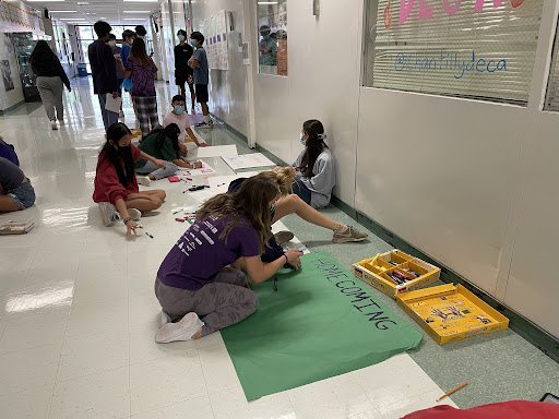 Leadership students decorate posters for the homecoming dance and football game. Homecoming is one long-standing high school tradition that emphasizes boys sports, as similar traditions are not present in girls sports.