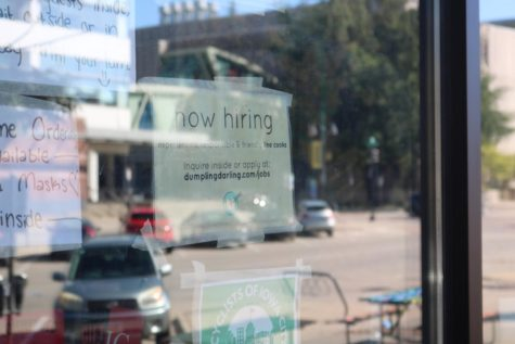 """A """"Now Hiring"""" sign hangs in the window of Dumpling Darling, a restaurant in downtown Iowa City,"""
