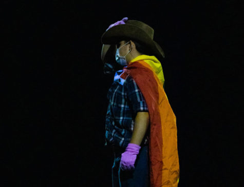 Senior drum major DJ Johnston leads the band during the halftime show on Sept. 24. Band members wore pride flags to show solidarity with students at Newberg after their school board banned teachers from being able to display it in classrooms.