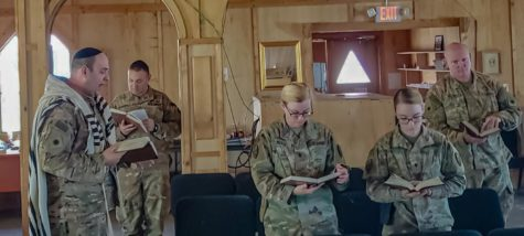"""CONNECTED: Jewish service members join together to engage in prayer while deployed in Afghanistan in 2018. U.S. Army chaplain Rabbi David Becker, left, led services for the soldiers, including U.S. Army Maj. Moses Scheinfeld, second from left; both live in Los Angeles. """"I try to lift them up,"""" said Rabbi Becker, who taught at Shalhevet. """"It's a very difficult time in a soldier's or military member's life to be deployed so far from home and everything they know."""""""